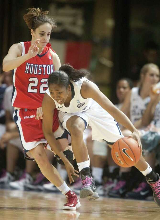 Rice guard Maya Adetula (22) drives against University of Houston guard Roxana Button (22) during the second half of a NCAA college basketball game at Tudor Field House on Thursday, February 23, 2012 in Houston, TX.   The Owls defeated the Cougars 68-40. Photo: J. Patric Schneider, For The Chronicle / Houston Chronicle