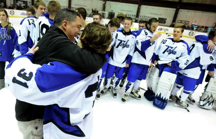 Saratoga's coach Dave Torres, center, embraces goalie Ryan Bourgeois (31) as they celebrate their win 5-1 over Shenendehowa for the Section II hockey title on Thursday, Feb. 23, 2012, at Union College in Schenectady, N.Y. (Cindy Schultz / Times Union) Photo: Cindy Schultz / 00016550A