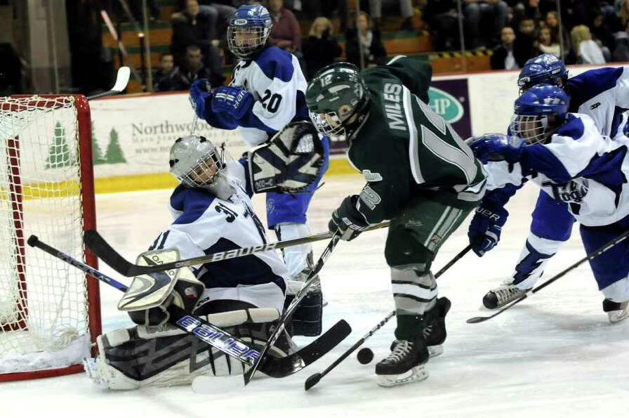 Saratoga's goalie Ryan Bourgeois (31), left, makes a save against Shenendehowa's Kevin Miles (12), c