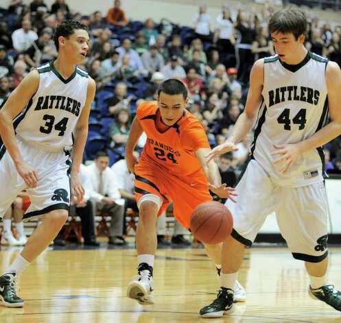 Brandeis' Jeremy Martinez, center, drives between Reagan's Jack Johnson, left, and D.J. MacLeay during a high school basketball playoff game, Thursday, Feb. 23, 2012, at UTSA in San Antonio. Brandeis won 52-43. Photo: Darren Abate, Express-News