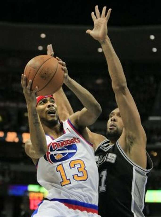 Denver Nuggets small forward Corey Brewer (13) scores past San Antonio Spurs center Tim Duncan (21) during the fourth quarter of an NBA basketball game on Thursday, Feb. 23, 2012, in Denver. The Spurs won 114-99. (AP Photo/Barry Gutierrez) (AP)