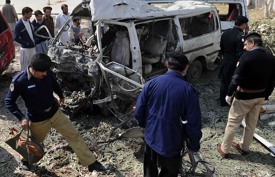 Pakistani policemen inspect a destroyed vehicle at the site of a car blast on the outskirts of Peshawar on February 23, 2012.  A car bomb ripped through a Pakistani bus station on February 23, killing 12 people, including two children on the outskirts of the northwestern city of Peshawar, officials said. Photo: A. Majeed, AFP/Getty Images