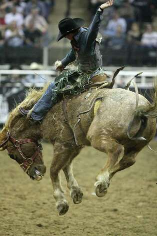 Jacobs Crawley, of College Station, rides in the Saddle Bronc competition at the San Antonio Stock Show & Rodeo at the AT&T Center on Wednesday, Feb. 22, 2012. Photo: Jerry Lara, San Antonio Express-News / © San Antonio Express-News
