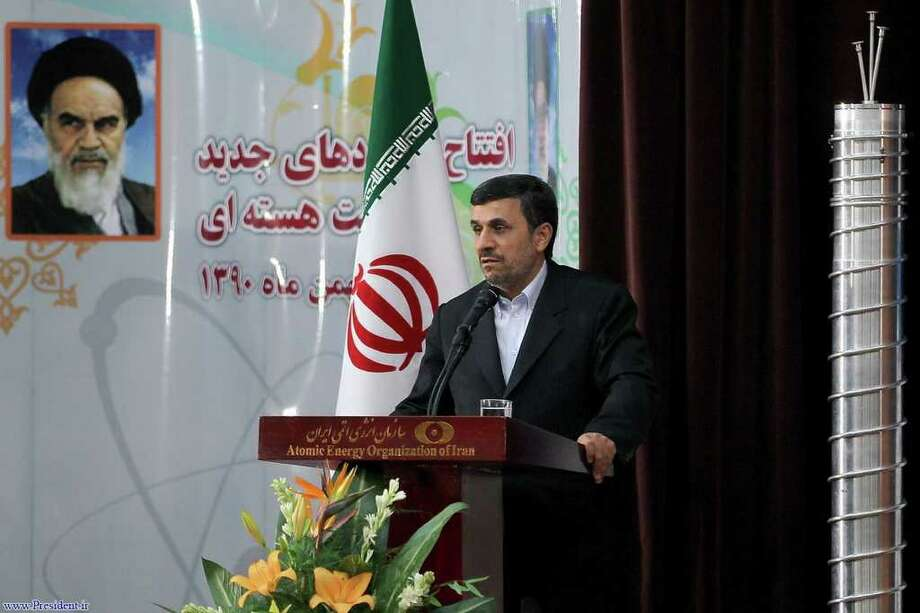 Iranian President Mahmoud Ahmadinejad, next to a poster of the late Ayatollah Khomeini, announces Iran is dramatically closer to mastering the production of nuclear fuel. Photo: Courtesy Iranian President's Office / Iranian President's Office