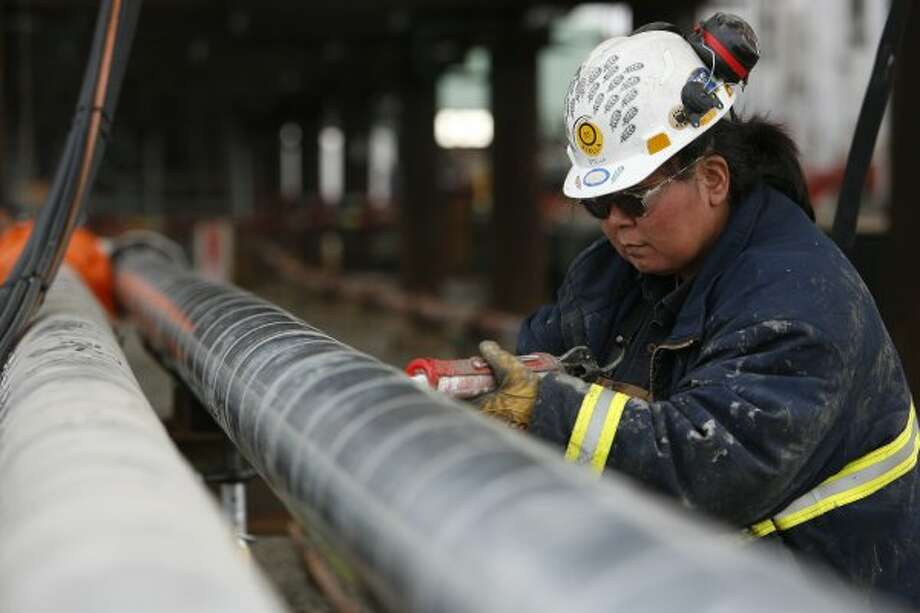 ConocoPhillips contractor Stella Castro seals insulation on a pipe at the CD2 Alpine oil field Friday, Sept. 21, 2007, on North Slope Borough, Alaska.  This photo accompanies a Tom Fowler business story. ( Kevin Fujii / Chronicle ) (Houston Chronicle)
