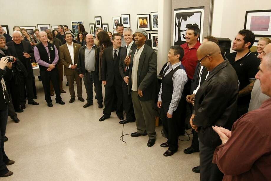 Lieutenant Dwayne Newtown (center), curator of the exhibit, invited all of the attending photographers to the front of the exhibit while he gave his speech.  The Harvey Milk Cultural Center held an exhibit on Friday February 3, 2012, showcasing photography by San Francisco firefighters and police officers. Photo: Sean Culligan, The Chronicle