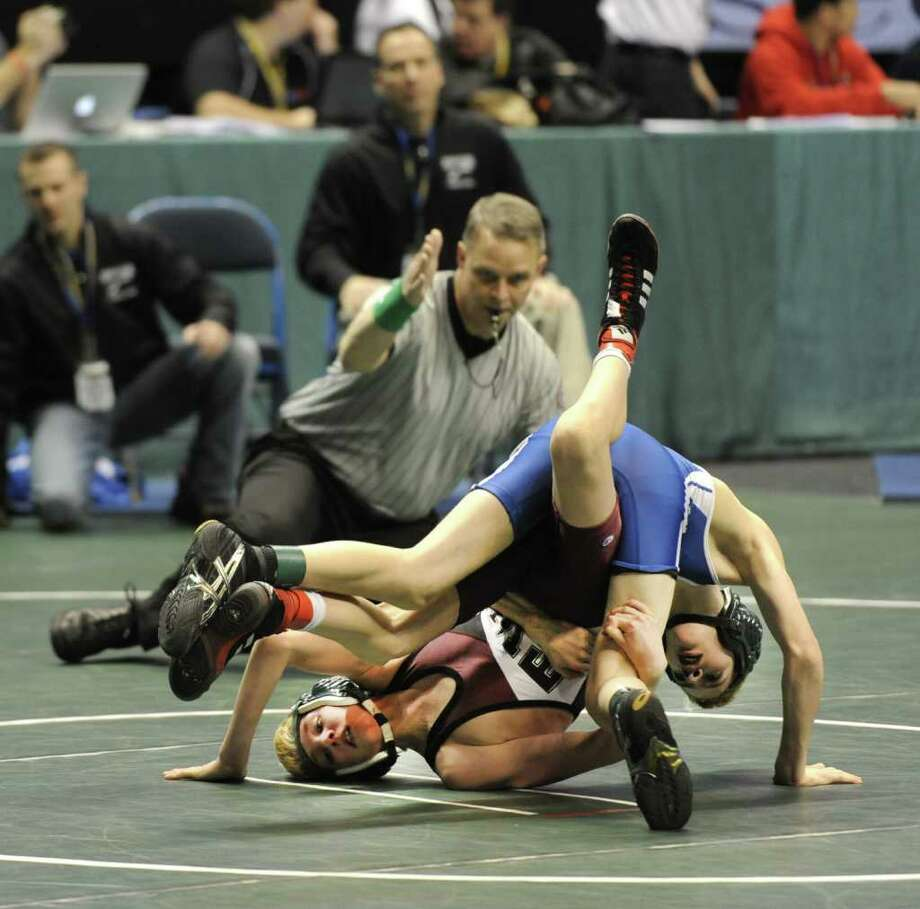 Gerard Daly of Minisink Valley High School, blue uniform outscored Kevin Parker of Shenendehowa High School 17-2 in the opening matches of the NYSPHSAA Wrestling State Championships which commenced today at the Times Union Center in Albany, N.Y. Feb. 24, 2012.        ( Skip Dickstein / Times Union) Photo: Skip Dickstein / 2011