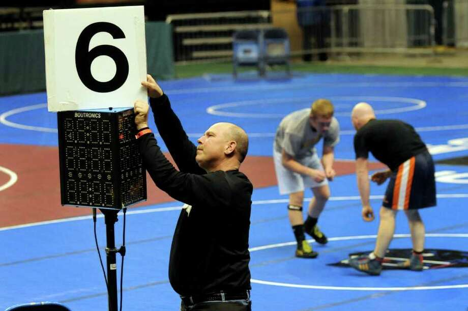 Section II coach Howard Weller of South Glens Falls, left, puts the finishing touches on the mat setup for practice time on Thursday, Feb. 23, 2012, at Times Union Center in Albany, N.Y. Weller said he's been setting up Section II championships for 25 years. The state wrestling tournament begins Friday. (Cindy Schultz / Times Union) Photo: Cindy Schultz / 00016531A