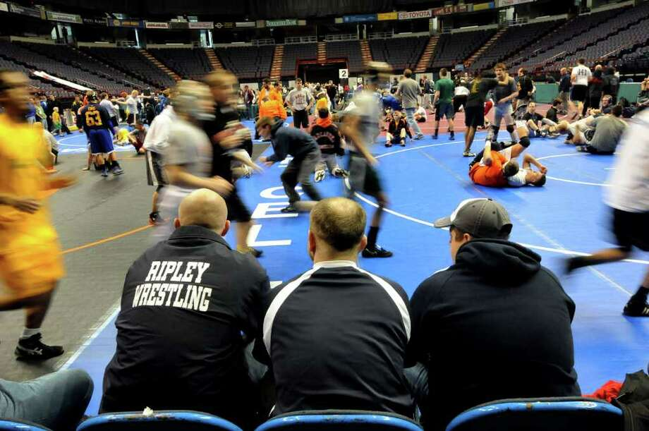 Section VI coaches from Chautaqua County watch as wrestlers warm up during practice time on Thursday, Feb. 23, 2012, at Times Union Center in Albany, N.Y. Coaches from left are Pete Dorman, Brad Rowe and Robbie Waddington. The state wrestling tournament begins Friday. (Cindy Schultz / Times Union) Photo: Cindy Schultz / 00016531A