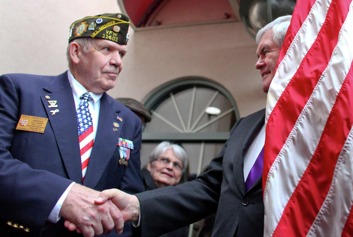U.S. presidential candidate Newt Gingrich shakes hands with VFW Commander Jack Chandler during a rally at a hotel in Federal Way on Wednesday February 14, 2012. A room filled with supporters at the hotel greeted the former Speaker of the House.