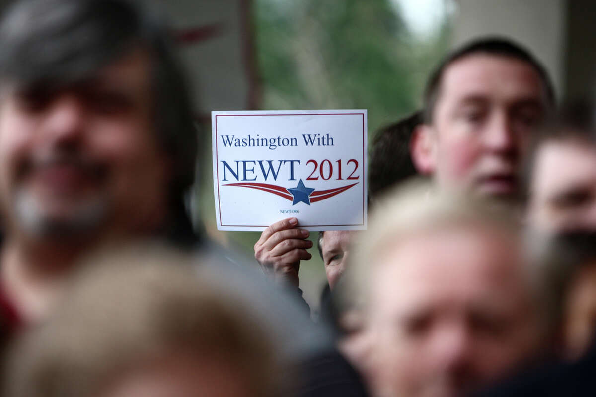 A supporter holds up a sign for U.S. presidential candidate Newt Gingrich outside of a rally at a hotel in Federal Way on Wednesday February 14, 2012. A room filled with supporters at the hotel greeted the former Speaker of the House.