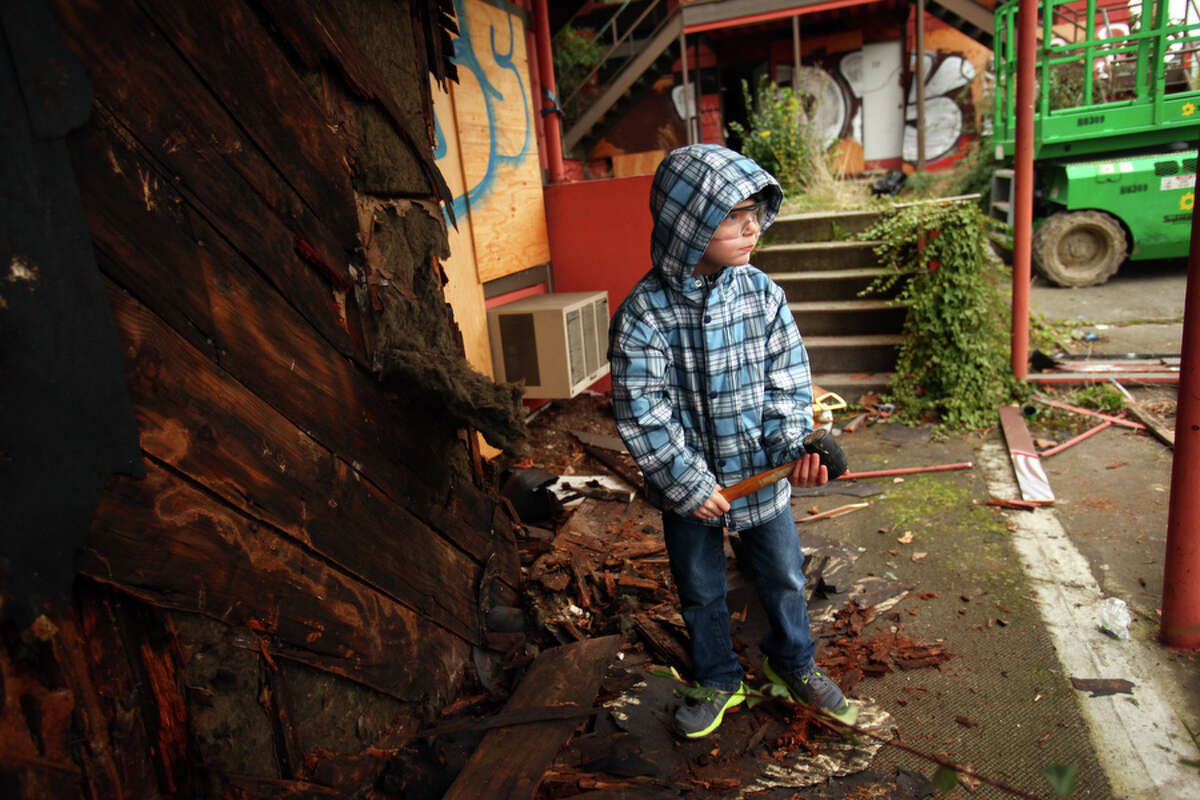 Zac Wise, 6, prepares to smash a wall with a hammer at the former site of the Thunderbird Inn on Wednesday February 14, 2012 on Aurora Avenue North in Seattle. Demolition on the long-troubled motel will begin on Tuesday but neighbors came out Friday to celebrate the beginning of the demolition process. It will be replaced by 71 units of affordable housing run by Catholic Housing Services.