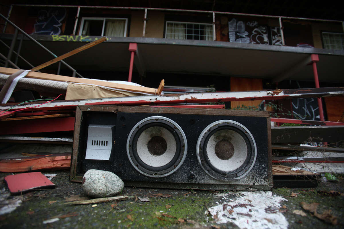 Speakers at the former site of the Thunderbird Inn are shown on Wednesday February 14, 2012 on Aurora Avenue North in Seattle. Demolition on the long-troubled motel will begin on Tuesday but neighbors came out Friday to celebrate the beginning of the demolition process. It will be replaced by 71 units of affordable housing run by Catholic Housing Services.