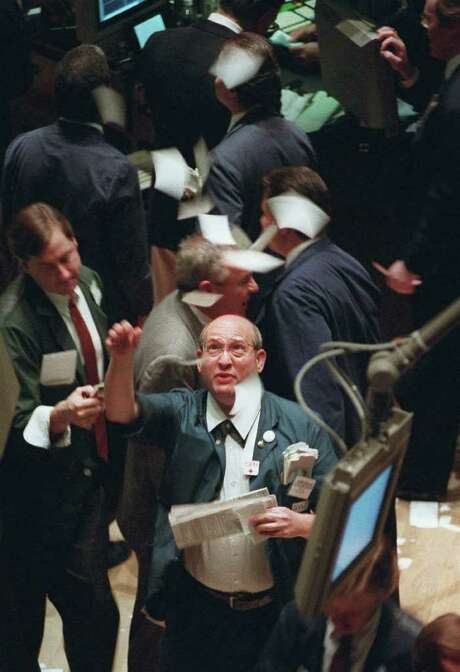 File - In this Nov. 21, 1995 file photo, a New York Stock Exchange trader throws tickets into the air on the floor of the exchange as it closes, in New York. The Dow Jones industrial average closed in record territory over the milestone 5,000 mark for the first time  in  history. When it comes to Wall Street, big, round numbers make people take notice. Dow 13,000, reached earlier this week for a few brief minutes, was the latest example. Photo: AP