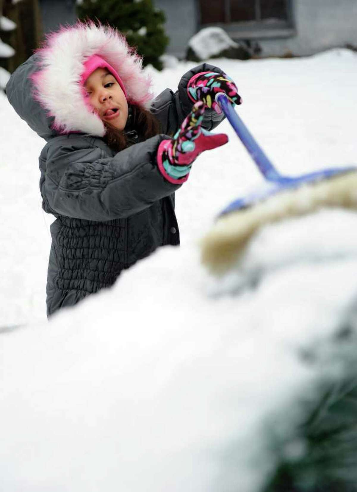 Six-year-old Krystiana Dukes helps clean the snow off her father's car in Derby Friday, Feb. 24, 2012 while waiting for the school bus outside her home.