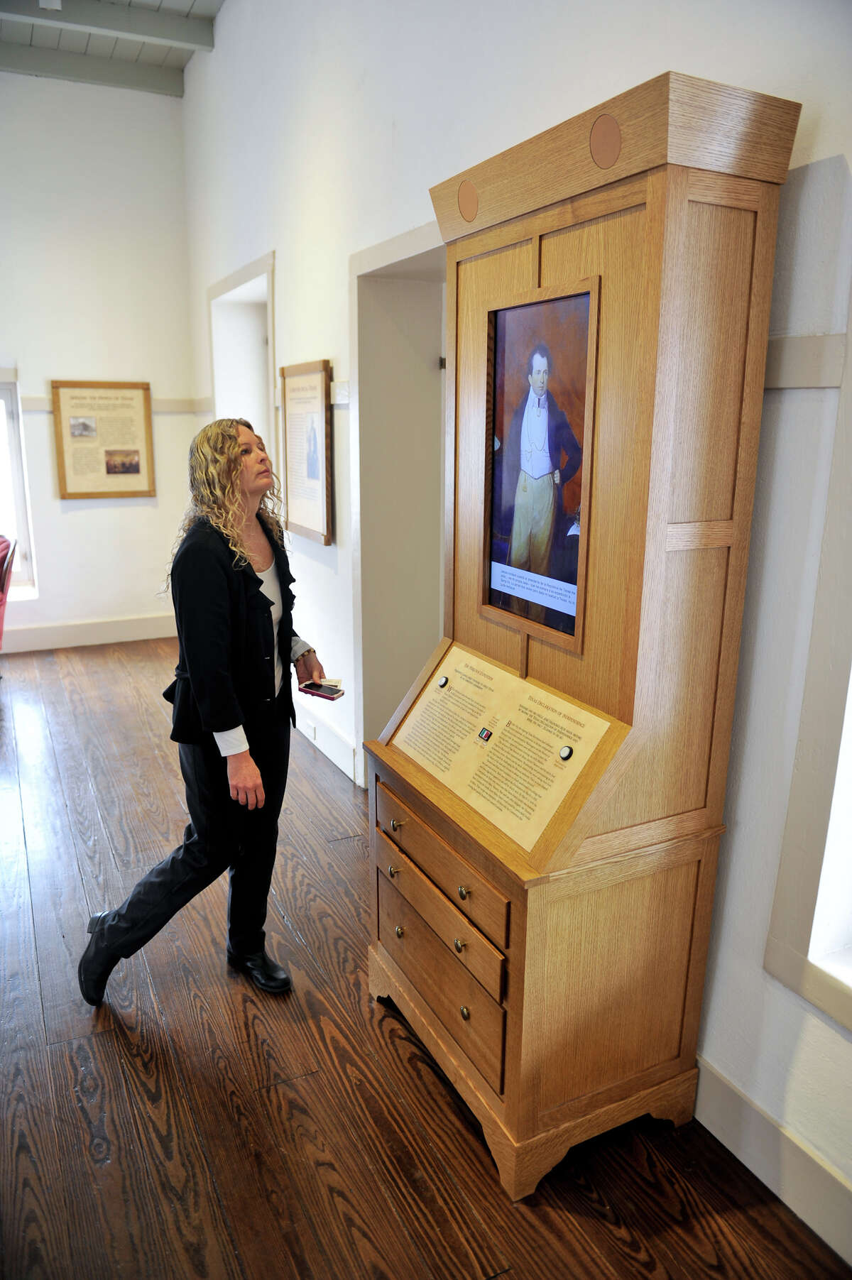 Casa Navarro State Historic site manager Maureen Brown looks over one of the interactive exhibits at the downtown location.