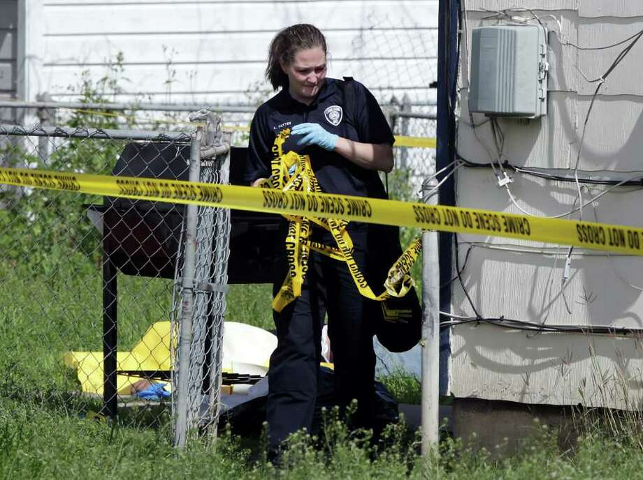 A member of the San Antonio Police Crime Scene Unit takes down police tape as they investigate the scene of a shooting at 239 Viendo near I-10 and Hildebrand Rd. Two individuals died from gunshot wounds.  Friday, Feb. 24, 2012. Bob Owen/Express-News Photo: BOB OWEN, San Antonio Express-News / © 2012 San Antonio Express-News
