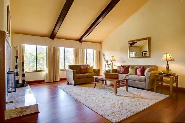 The living room's features include hardwood flooring, neutral wall coloring and a fireplace with a beautiful white marble surround. Photo: Jason Wells