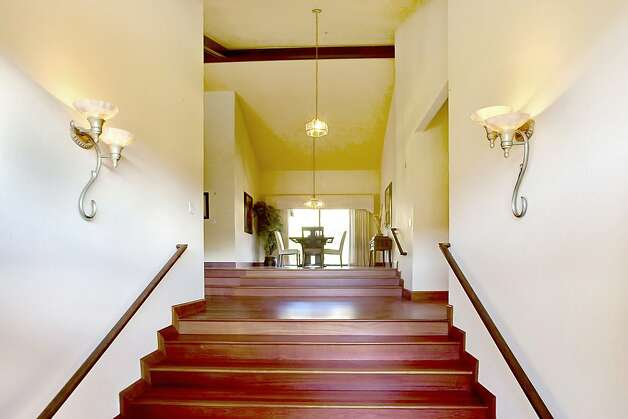 The entryway opens to hardwood-flooring stairs and into the formal dining room. From there, the rear patio can be accessed for an al fresco dining option. Photo: Jason Wells