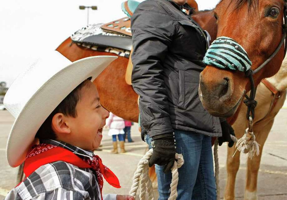 Fernando Ramirez, 4, a student from the Garden Oaks Elementary School's Children's House laughs after greeting a horse from the Spanish Trail ride group in the parking lot of a Sear's department store on the 4000 block of N. Shepherd Dr. Photo: Johnny Hanson, Houston Chronicle / © 2012  Houston Chronicle