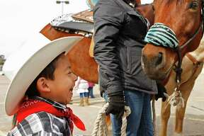 Fernando Ramirez, 4, a student from the Garden Oaks Elementary School's Children's House laughs after greeting a horse from the Spanish Trail ride group in the parking lot of a Sear's department store on the 4000 block of N. Shepherd Dr.