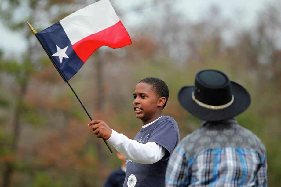 Jordan Johnson, a student at Stepping Stones School, holds up a Texas Flag as he waits to see the Trail Riders arrive at Memorial Park. Photo: Mayra Beltran, Houston Chronicle / © 2012 Houston Chronicle