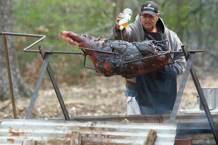 Arthur Ramirez cooks a slab of beef for the Los Vaqueros Trail Ride which is due to arrive at Memorial Park on Friday, Feb. 24, 2012, in Houston. Photo: Mayra Beltran, Houston Chronicle / © 2012 Houston Chronicle