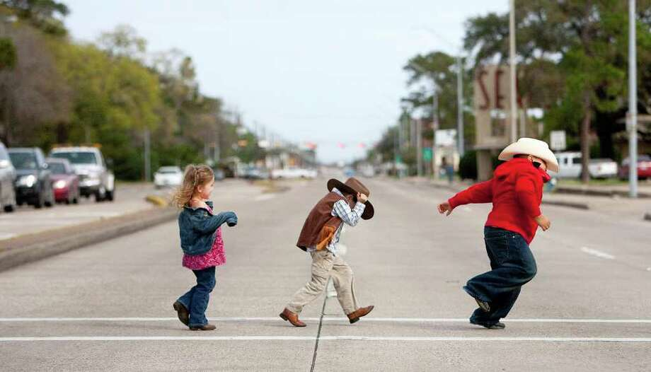 Students, from left, Kendy Taylor, Owen Winston and Francisco Diaz, walk across the street to  greet trail riders with the Spanish Trail group. Photo: Johnny Hanson, Houston Chronicle / © 2012  Houston Chronicle