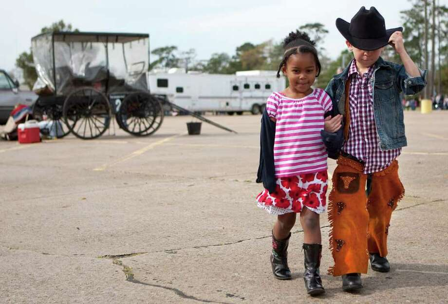 Luke Newman, 6, and Anabelle McClain, 4, walk arm-in-arm as a group of students from the Garden Oaks Elementary School's Children's House met trail riders with the Spanish Trail Rider's group. Photo: Johnny Hanson, Houston Chronicle / © 2012  Houston Chronicle