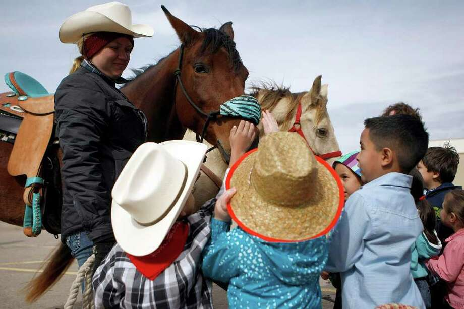 A group of students from the Garden Oaks Elementary School's Children's House met with trail riders from the Spanish Trail ride group including Haley Krampus, 19. The students had the opportunity to meet the trail riders, ask questions, touch horses and get a look inside a wagon. Photo: Johnny Hanson, Houston Chronicle / © 2012  Houston Chronicle