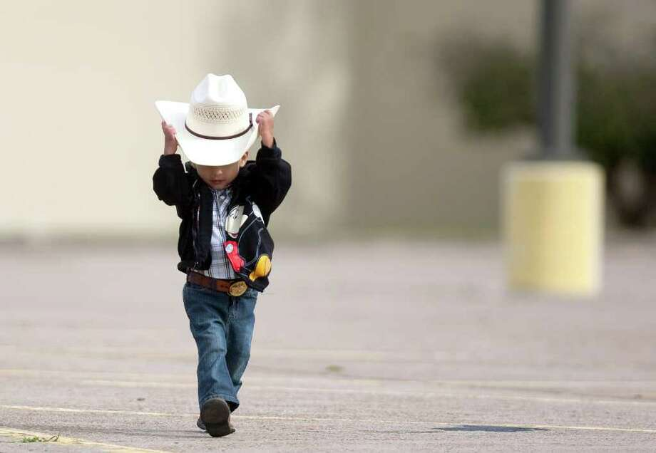 Wearing his Go Texan Day apparel, Adrian Cardona, 3, walks to greet riders with the Spanish Trail Rider's group in the parking lot of a Sear's department store where the group spent the night before they made their three-hour ride to Memorial Park. The Spanish Trail riders group began their 109 mile journey in Shepherd. Photo: Johnny Hanson, Houston Chronicle / © 2012  Houston Chronicle