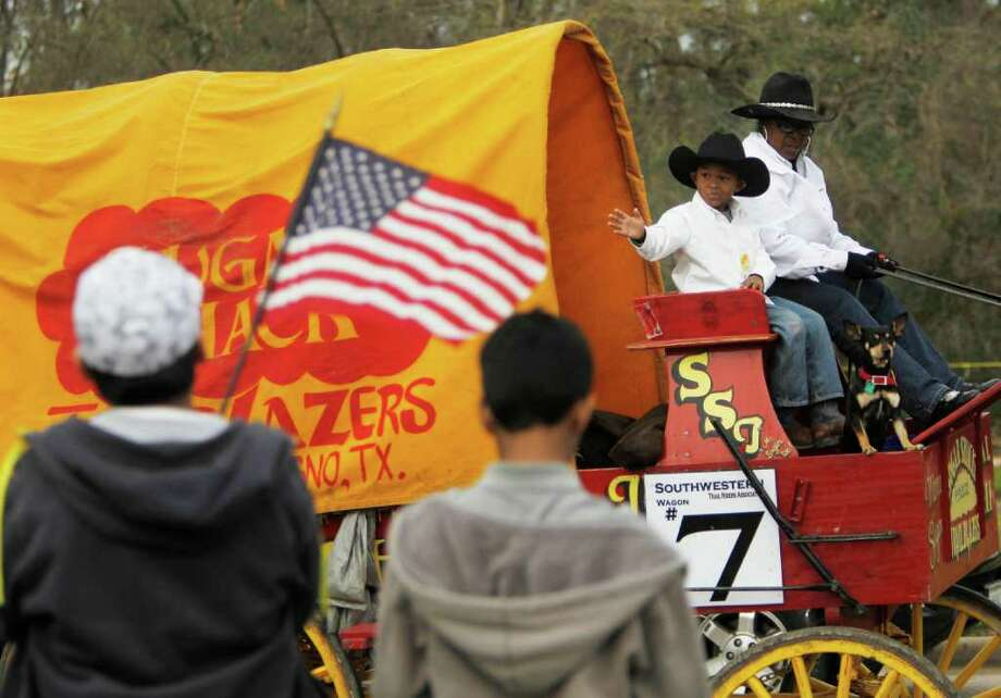Tyler Darden, 6, and Beverlyn Sanders ride with the Southwestern Trail Riders Association as they arrive at their campsite at Memorial Park. Photo: Mayra Beltran, Houston Chronicle / © 2012 Houston Chronicle