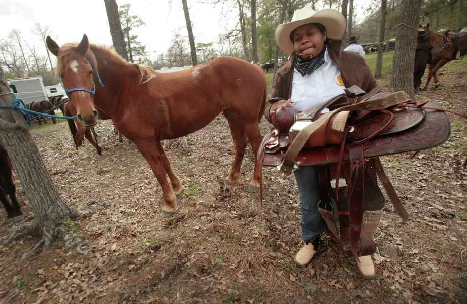 Magan Brown settles into camp by roping her horse and removing it's saddle upon arrival at Memorial Park. Photo: Mayra Beltran, Houston Chronicle / © 2012 Houston Chronicle
