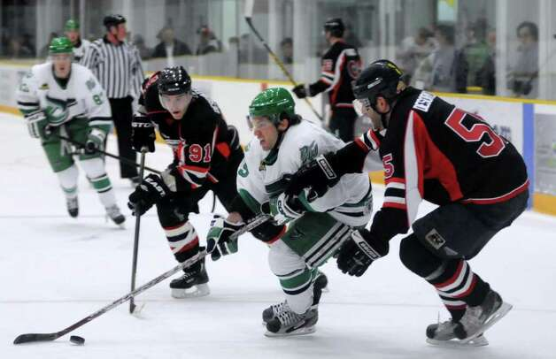 The Akwesasne Warriors played against the Danbury Whalers at the Danbury Arena on Friday Feb. 24, 2012.      From left, Warriors Sylvain Deschatelets, Whalers Greg Holt and Warriors Simon Desormeaux fight for possession. Photo: Lisa Weir / The News-Times Freelance