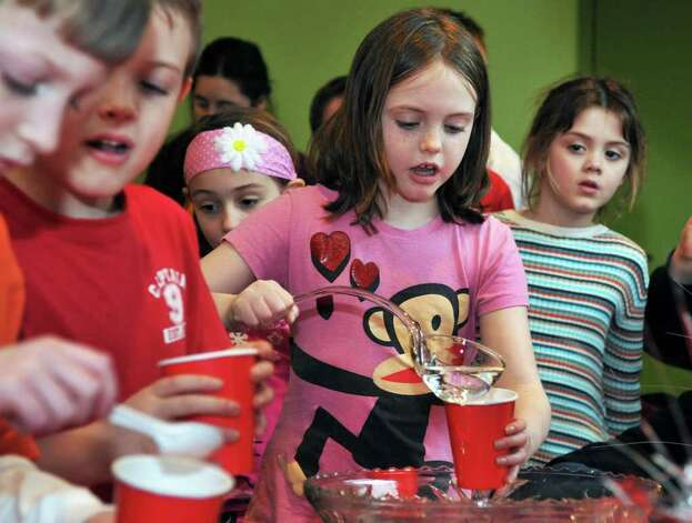 "Grace Earley, center, 8, of Schuylerville mixes up a ""Luck Potion"" with other children during a Harry Potter party at the Children?s Museum at Saratoga Friday Feb. 24, 2012.   (John Carl D'Annibale / Times Union) Photo: John Carl D'Annibale / 00016488A"