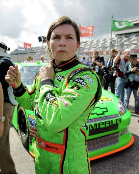 Danica Patrick removes her earplugs as she stands by he car after her qualifying run for the NASCAR Daytona 500 auto race at Daytona International Speedway, Sunday, Feb. 19, 2012, in Daytona Beach, Fla. Photo: AP