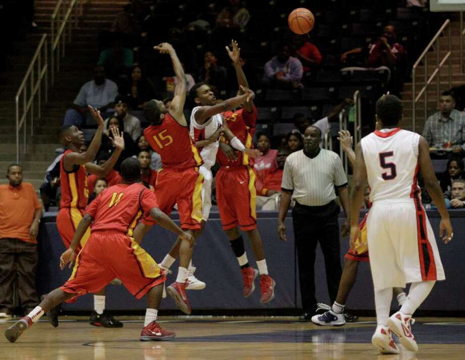 2/24/12: Maurice Ellis #15 of Yates Lions and teammates was all over  Jalen Hatch #4 and his teammates of the Manvel Mavericks in a mens high school playoff  basketball game at Coleman Coliseum For the Chronicle: Thomas B. Shea Photo: Thomas B. Shea, For The Chronicle / © 2011 Thomas B. Shea