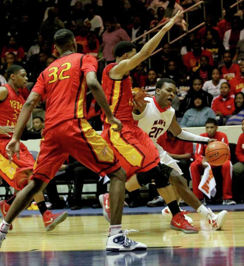 2/24/12: Terry Allen #20 of Manvel Mavericks dribbles past Clyde Santee  #32 of Yates Lions in a mens high school playoff  basketball game at Coleman Coliseum For the Chronicle: Thomas B. Shea Photo: Thomas B. Shea, For The Chronicle / © 2011 Thomas B. Shea