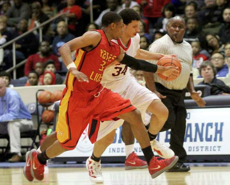 2/24/12: Traylin Farris #34 of Manvel Mavericks has the ball stolen by Chris Wells  #33 of Yates Lio