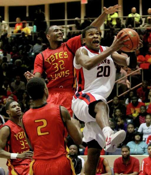 2/24/12: Terry Allen #20 of Manvel Mavericks has his shot blocked by Clyde Santee  #32 of Yates Lion