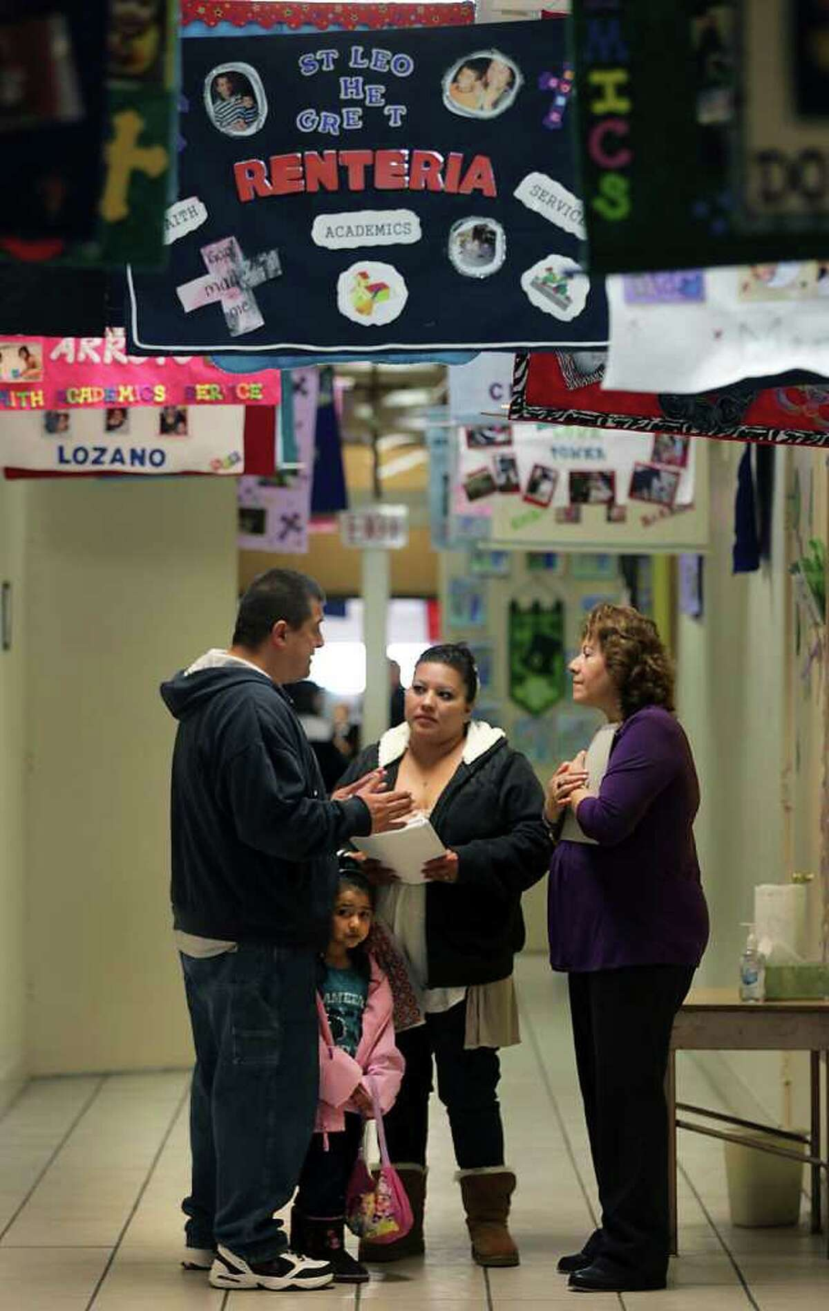 Alma Rodriguez, right, Office Manager at St. Leo the Great Catholic School, listens to questions from Douglas Ramirez, left, as he and his wife Veronica, center, take a tour of the school to enroll their 3 year old daughter Victoria. In the hall hang family banners rerpresenting the families that attend the school. Students and faculty at St. Leo the Great Catholic School will see an increase in the student body as The Archdiocese of San Antonio announced the closing of St. Cecilia and St. Philip of Jesus schools.