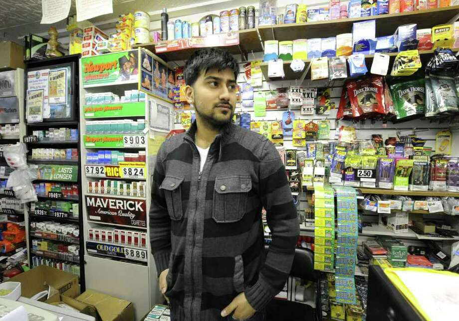 Shoaib Munir works the front counter of the A-Z Capital Central Mart on Central Avenue in Albany, N.Y. Feb. 24, 2012.  ( Skip Dickstein / Times Union) Photo: Skip Dickstein / 00016571A