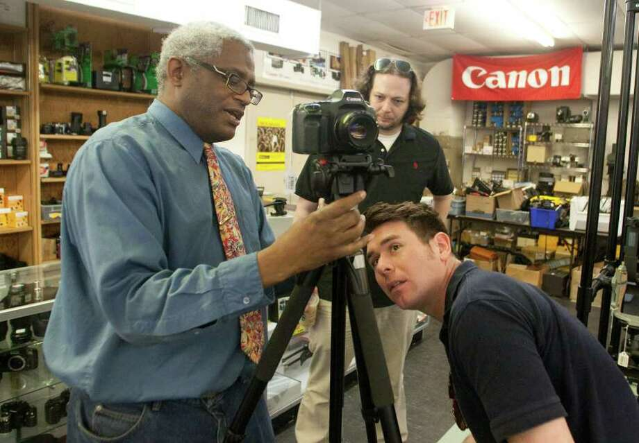 Salesman Erwin Ferguson, left, helps Chris Brown and Justin Fuqua, background, select a tripod at Houston Camera Co-op. Many local retailers are surviving online competition by focusing on customer service and offering specialized products and services. Photo: J. Patric Schneider / Houston Chronicle