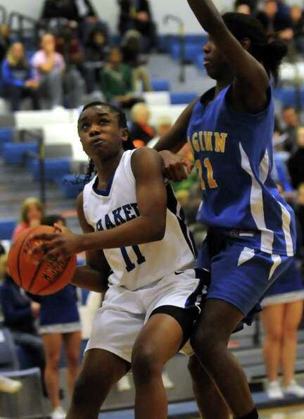 Shaker's Adriene Gambles (11), left, looks to the hoop as Bishop Maginn's Kayla Miller (11) defends