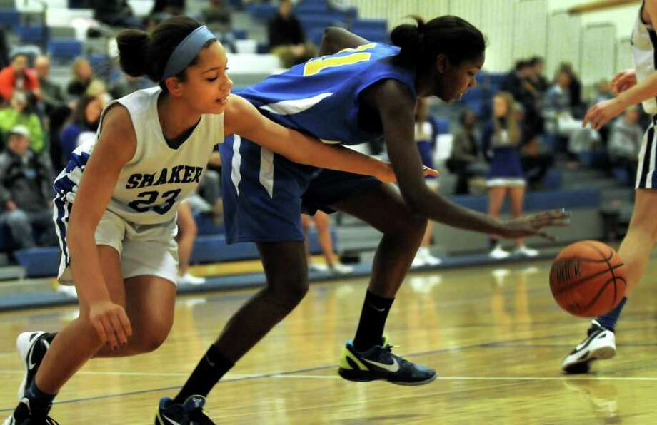 Shaker's Merrick Rowland (23), left, and Bishop Maginn's Kayla Miller (11) pursue a loose ball during their Class AA quarterfinal basketball game on Friday, Feb. 24, 2012, at Shaker High in Latham, N.Y. (Cindy Schultz / Times Union) Photo: Cindy Schultz / 00016562A