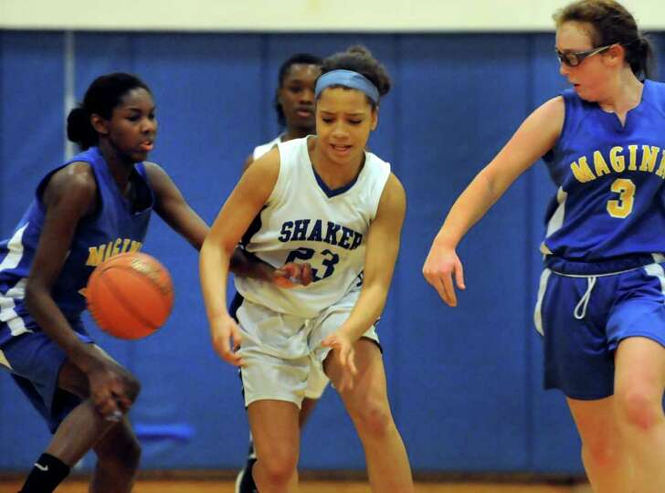 Shaker's Merrick Rowland (23), center, loses the ball against Bishop Maginn's Kayla Miller (11), lef