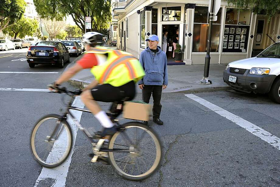 Bruce Marshall watches cyclists run through the stop sign on the corner of Steiner and Waller in San Francisco, CA Friday Feb. 24th, 2012.  Bruce has complained that cyclists run the stop sign as the turn right from Waller St. onto Steiner St. which is  endangering pedestrians that are trying use the cross walk. Photo: Michael Short, Special To The Chronicle