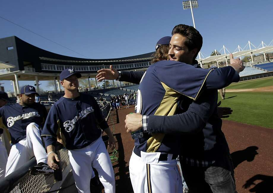 Milwaukee Brewers' Ryan Braun, right, gets a hug from teammate John Axford after a news conference at spring training baseball, in Phoenix, Friday, Feb. 24, 2012. National League MVP Braun's 50-game suspension was overturned by baseball arbitrator Shyam Das on Thursday, the first time a baseball player successfully challenged a drug-related penalty in a grievance.(AP Photo/Jae C. Hong) Photo: Jae C. Hong, Associated Press