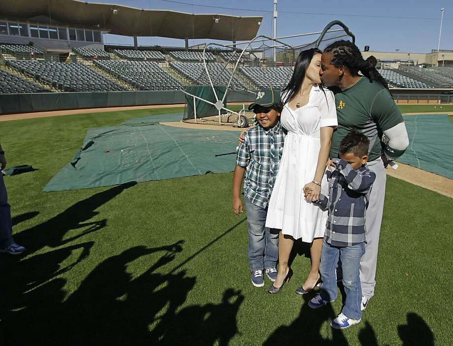 Oakland Athletics' Manny Ramirez gives his wife, Juliana, a kiss following a spring training baseball workout Friday, Feb. 24, 2012, in Phoenix. Manny Jr. at left while Lucas is at right. (AP Photo/Darron Cummings) Photo: Darron Cummings, Associated Press