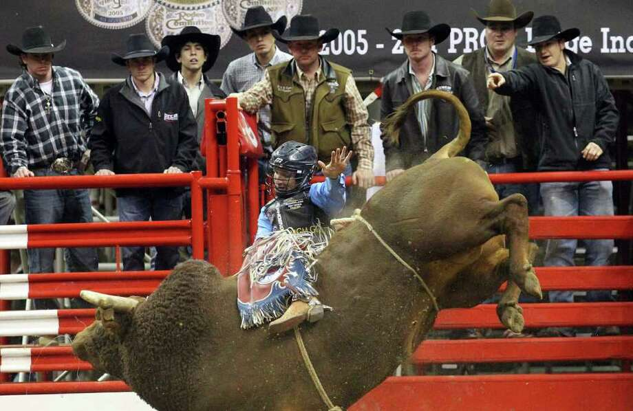 J.W. Harris attempts to hold while riding Little Snake during the Bull Riding competition at the 2012 San Antonio Stock Show & Rodeo on Friday, Feb. 24, 2012. Kin Man Hui/San Antonio Express-News Photo: Kin Man Hui, SAN ANTONIO EXPRESS-NEWS / ©2012 SAN ANTONIO EXPRESS-NEWS